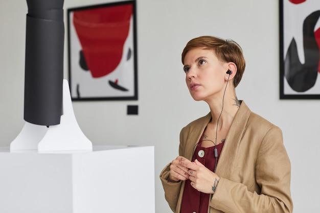 Портрет современной молодой женщины, смотрящей на скульптуры и слушающей аудиогид на выставке в художественной галерее,