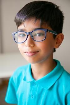 Портрет довольного азиатского маленького мальчика в очках