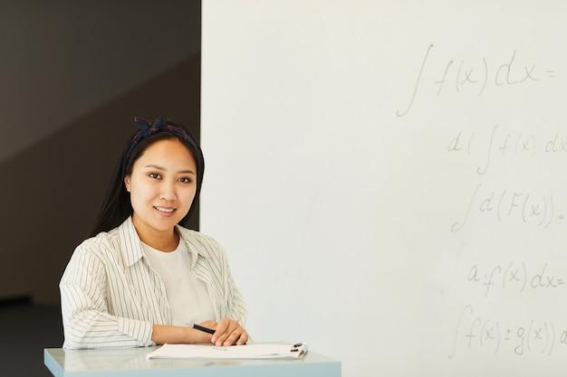 Портрет довольной привлекательной азиатской студентки, стоящей на лекционной стойке с бумагами на доске в классе