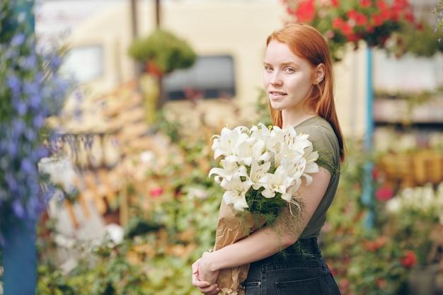 Портрет довольной привлекательной рыжей девушки, работающей с цветами на растительном рынке, она держит белые лилии в бумаге