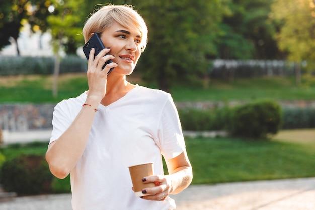 緑の公園を散歩中に携帯電話で話し、持ち帰り用のコーヒーを保持しながら、笑顔でカジュアルな服を着ている魅力的な女性のコンテンツの肖像画