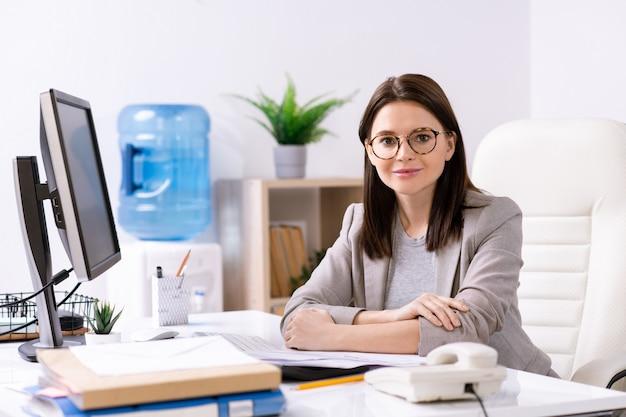 コンピューター、書類、電話で机に座っているジャケットの魅力的な若いオフィスマネージャーのコンテンツの肖像画
