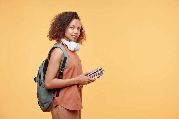 コンテンツの肖像黄色の背景にワークブックを保持しているアフロの髪型を持つ黒い女子高生