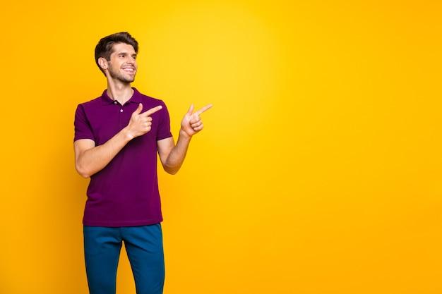 Портрет довольного веселого радостного парня в сиреневой рубашке, указывающего двумя указательными пальцами на рекламу как изолированные
