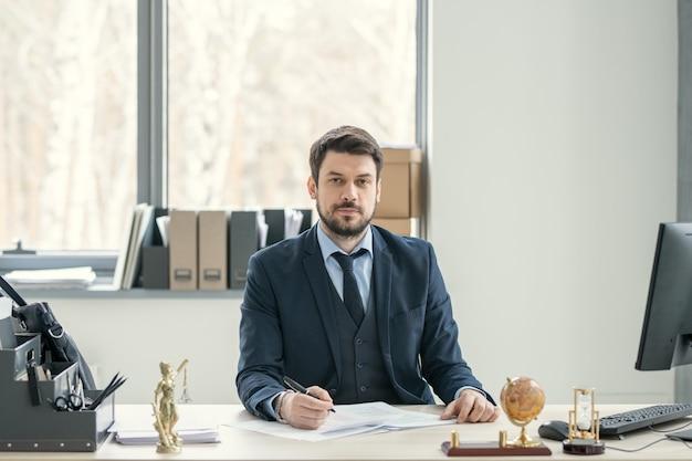 Портрет довольного красивого бородатого адвоката в костюме, сидящего за столом и изучающего документы в офисе