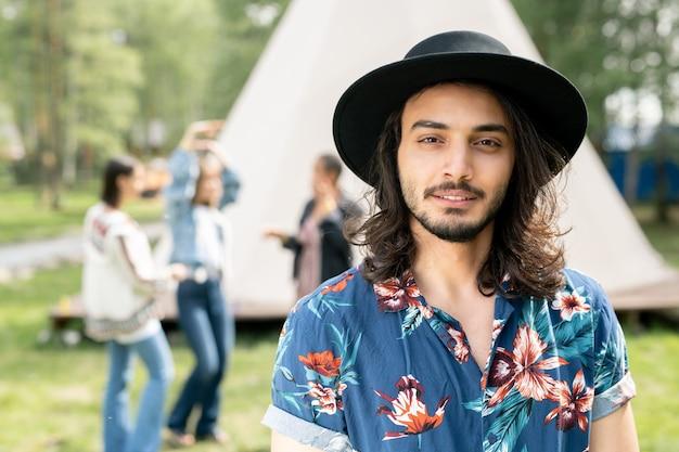 Портрет довольного красивого еврейского парня в черной шляпе и рубашке с цветочным принтом, отдыхающего с друзьями в лесном кемпинге