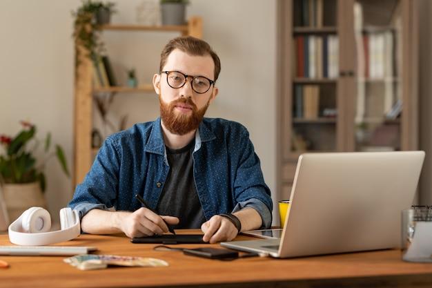 ホームオフィスの描画パッドとラップトップとテーブルに座っている眼鏡のコンテンツハンサムな若い男性イラストレーターの肖像画