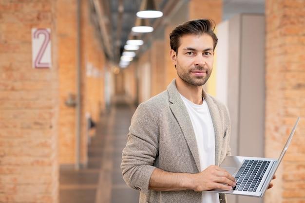 無精ひげコワーキングスペースに立っていると現代のラップトップを保持しているコンテンツのハンサムな若い男の肖像