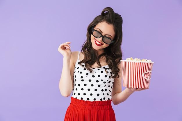 복고 폴카 도트 드레스를 입은 콘텐츠 핀업 여성의 초상화와 보라색 벽에 격리된 영화를 보면서 팝콘이 든 양동이를 들고 있는 3d 안경