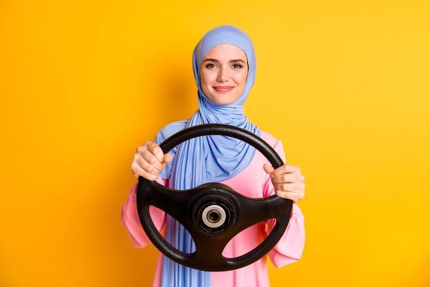 밝은 노란색 배경에 격리된 보이지 않는 자동차 임대를 운전하는 히잡을 쓴 꽤 쾌활한 이슬람교도의 초상화