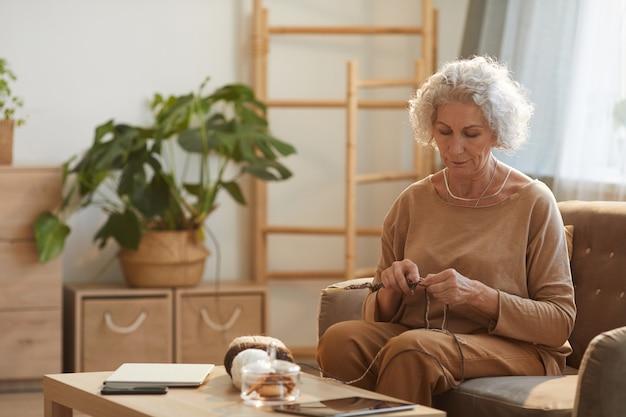 햇빛에 의해 조명 아늑한 집에서 뜨개질 콘텐츠 수석 여자의 초상화