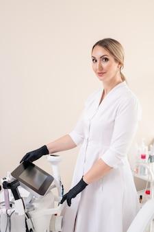 Портрет довольного молодого косметолога в белом халате и черных латексных перчатках готовится к лазерной процедуре в салоне красоты