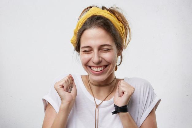 喜びで拳を握りしめ、笑顔で満足している女性の肖像画。