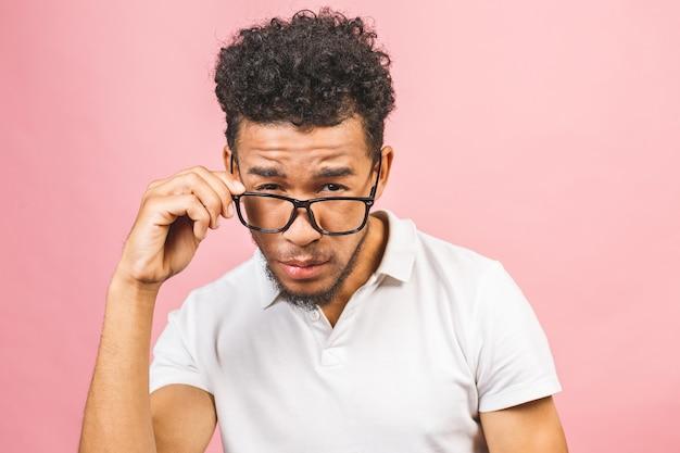 ピンクの背景に対して隔離される眼鏡を浮かべてカメラを見てクールでハンサムなアフリカの男性学生の肖像画。