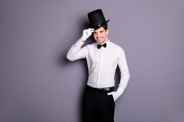 Портрет крутого привлекательного волшебника, готового выступить на цирковой сцене, сенсорный цилиндр, черная шляпа, белая классическая рубашка, брюки с бантом, перчатки, изолированные на серой стене