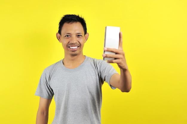 노란색 배경에 격리된 전면 카메라에서 셀카를 촬영하는 손에 스마트 폰을 들고 연인과 화상 통화를 하는 멋지고 쾌활한 아시아 남자의 초상화