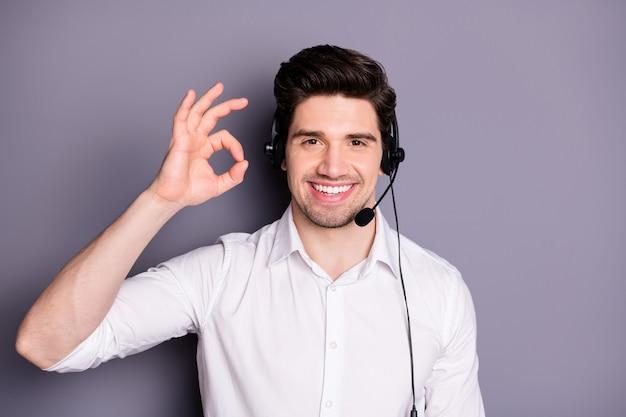 멋진 자신감 고객 지원 작업자의 초상화는 고객과 함께 도움을 줄 수 있습니다. 훌륭한 피드백 쇼 괜찮아 기호 착용 헤드셋 공식적인 마모 의류는 회색 벽 위에 절연