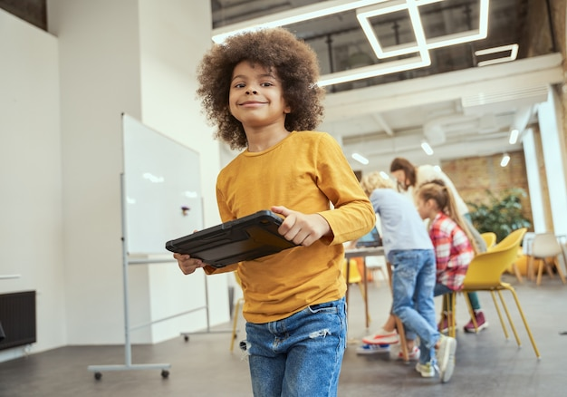 줄기 동안 교실에 서 있는 태블릿 pc를 들고 카메라를 보고 웃고 있는 멋진 소년의 초상화