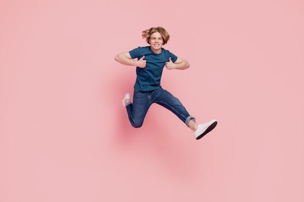 멋지고 믿을 수 있는 매력적인 남자 점프 달리기의 초상화는 분홍색 배경에 엄지손가락을 들어 올립니다