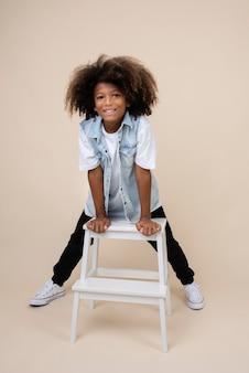 의자에 포즈를 취하는 멋진 10대 소년의 초상화