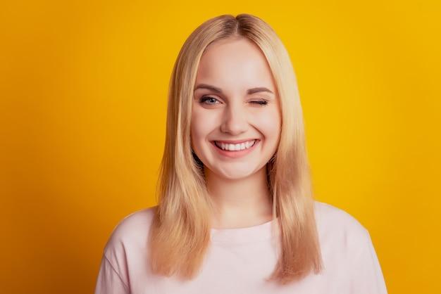 요염한 사랑스러운 여성의 초상화는 노란색 배경에 눈을 깜박이는 이빨 빛나는 미소