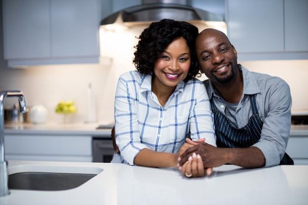 キッチンでお互いを受け入れてカップルの肖像画