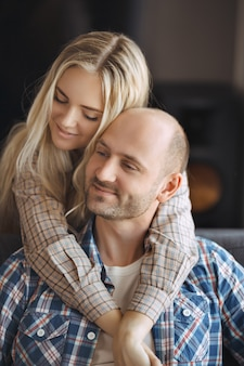 自宅のソファーを受け入れるカップルの肖像画