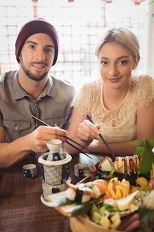寿司を持っているカップルの肖像画