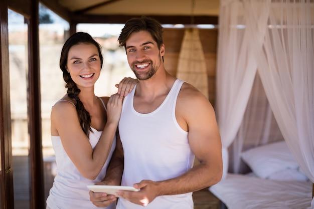 Портрет пары держа цифровую таблетку в коттедже