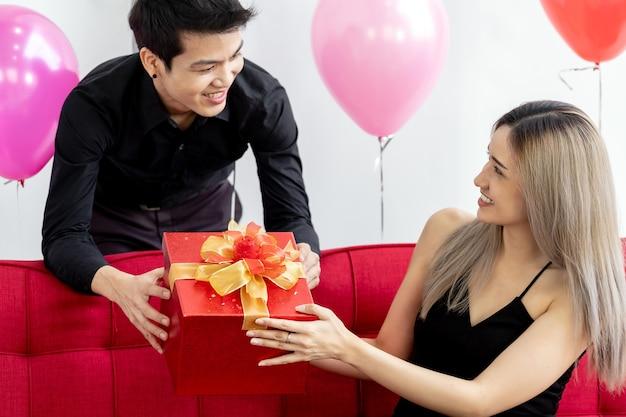 リビングルームでプレゼントを祝うギフトボックスプレゼントを持っているカップルの肖像画