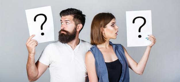 Портрет пары, держащей бумажный вопросительный знак. пара о чем-то думает. запутанные пары с вопросительными знаками. конфликт между двумя людьми. задумчивый мужчина и задумчивая женщина, конфликт.
