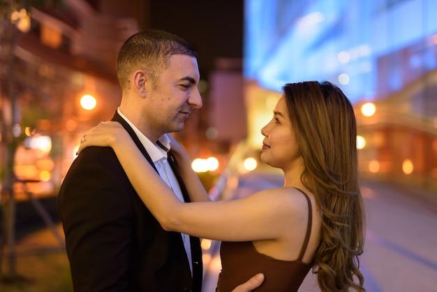 Портрет пары, глядя друг на друга на открытом воздухе ночью в городе в бангкоке, таиланд