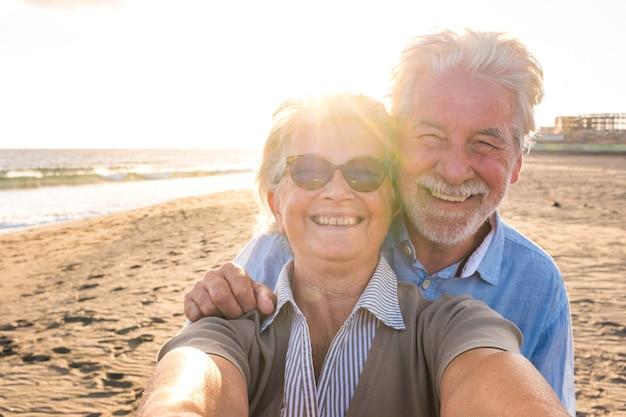 해변에서 여름을 즐기는 노년 부부의 초상화는 배경에서 일몰과 함께 셀카를 찍는 카메라를 바라보고 있습니다. 야외 여행을 하는 두 명의 활동적인 노인들.