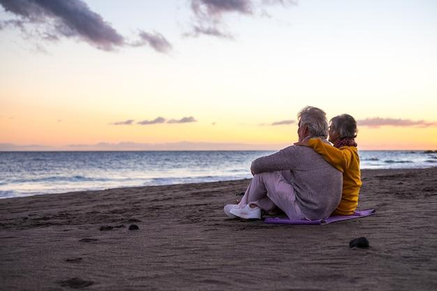 Портрет пары пожилых и старых людей, наслаждающихся летом на пляже, глядя на море, улыбаясь и весело вместе с закатом на заднем плане. два активных пожилых человека путешествуют на свежем воздухе.
