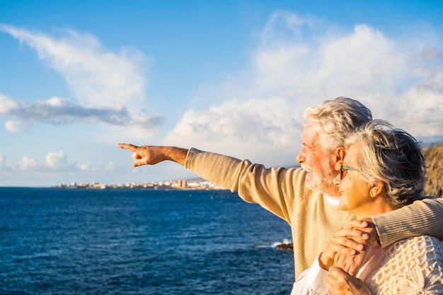 Портрет пары пожилых и пожилых людей, наслаждающихся летом на пляже, глядя на море, улыбаясь