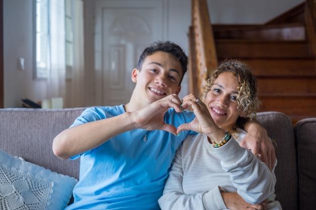 엄마와 아들 부부가 함께 집에서 손가락과 손으로 얼굴을 배경으로 하트 모양을 만드는 초상화. 다정한 십 대와 즐기는 여자