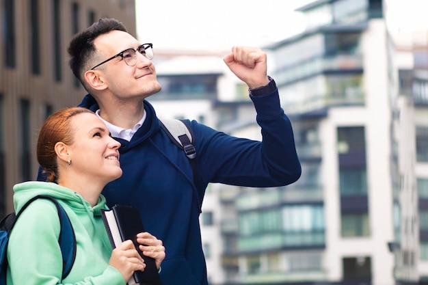 キャンパスの屋外で2人の美しい幸せな大学生のカップルの肖像画