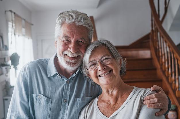 笑顔でカメラを見ている2人の幸せで健康な高齢者の老人のカップルの肖像画。家の屋内で一緒に楽しんで楽しんでいる成熟した祖父母のクローズアップ。