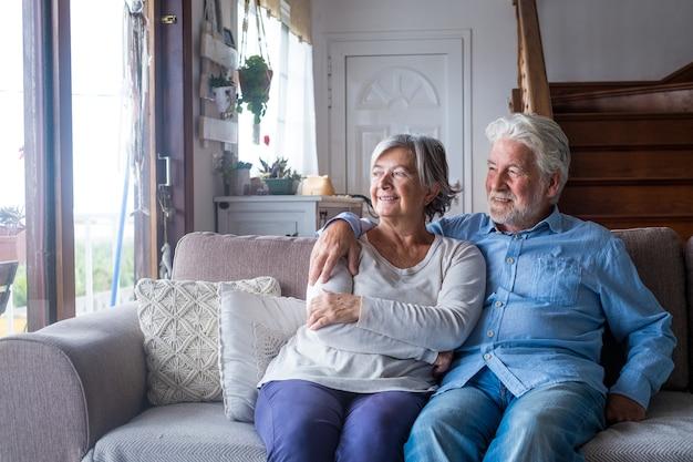 笑顔で窓を見ている2人の幸せで健康な高齢者の老人のカップルの肖像画。屋内のソファで一緒に楽しんで楽しんでいる成熟した祖父母のクローズアップ。