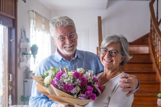 カメラを見て家で花を持っている2人の幸せで恋をしている先輩または成熟した老人のカップルの肖像画。一緒に休日を楽しんで祝う年金受給者の大人。