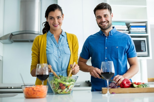 自宅のキッチンで一緒に食事を準備するカップルの肖像画