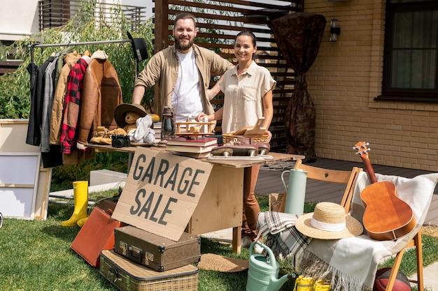 Портрет пары, продающей вещи из гаража на заднем дворе
