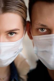 医療マスクを身に着けているカップルの肖像画をクローズアップ