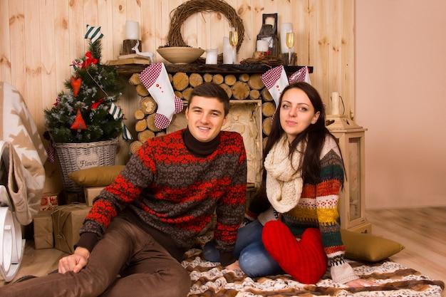 冬にログキャビン内の床に座っているセーターを着ているカップルの肖像画