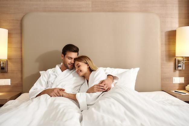 흰색 목욕 가운을 입고 침대에 누워 서로를 안고 있는 부부의 초상화. 함께 여행하는 개념. 가로 샷입니다. 전면보기