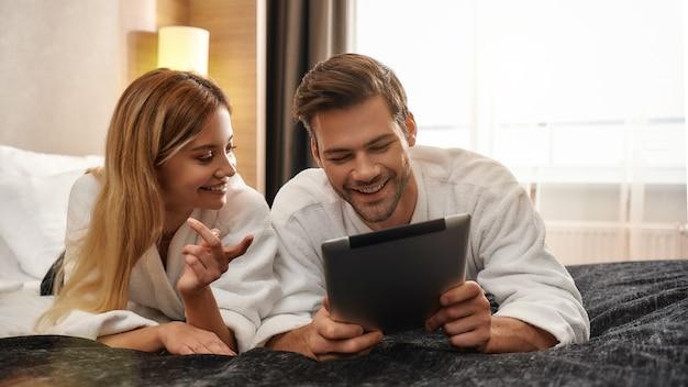 하얀 목욕 가운을 입고 침대에 누워 태블릿 pc 화면을 바라보는 커플의 초상화. 함께 여행하는 개념. 가로 샷입니다. 전면보기