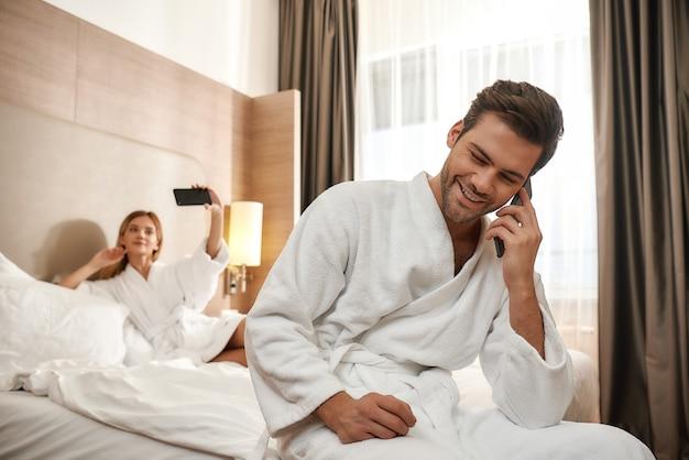 흰색 목욕 가운을 입고 커플의 초상화입니다. 남자는 침대 가장자리에 앉아서 여자가 셀카를 찍는 동안 전화로 이야기합니다. 함께 여행하는 개념. 가로 샷
