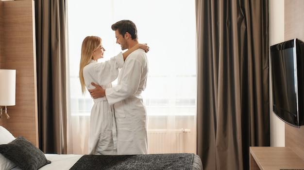 창 근처에 서 있는 흰색 목욕 가운을 입은 커플의 초상화. 함께 여행하는 개념. 가로 샷