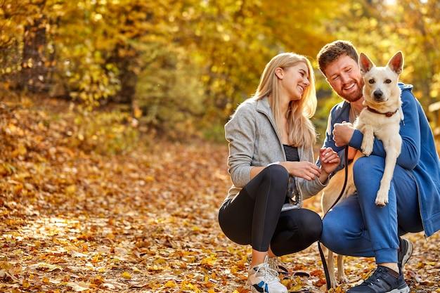 田舎、秋の晴れた日の森の中で親切な白いペットの犬とカップルの肖像画。黄色いオレンジの木とその周りの葉。人と動物の概念