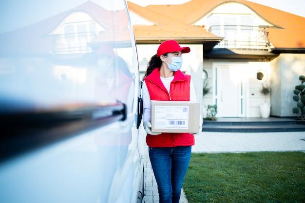 Портрет курьера, держащего посылки в своем фургоне, готовые к доставке во время пандемии коронавируса